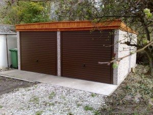 A double Pent garage with timer fascia and brown roller garage doors