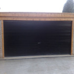 Pent double garage with timber front and brown roller door